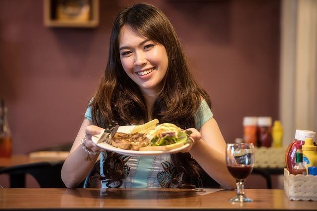 mladá štíhlá žena se těší na chutný oběd